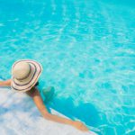 Clubes: jovem mulher relaxando na piscina