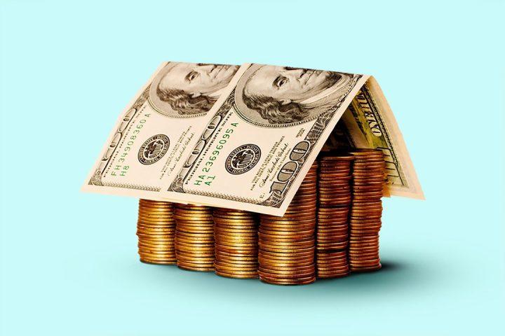 Condomínios fechados: pilha de moedas com cédula de dinheiro por cima, em formato de casa
