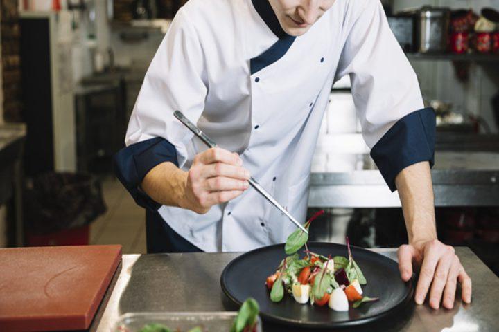 Opções culinárias: cozinheiro colocando espinafre em um prato com salada