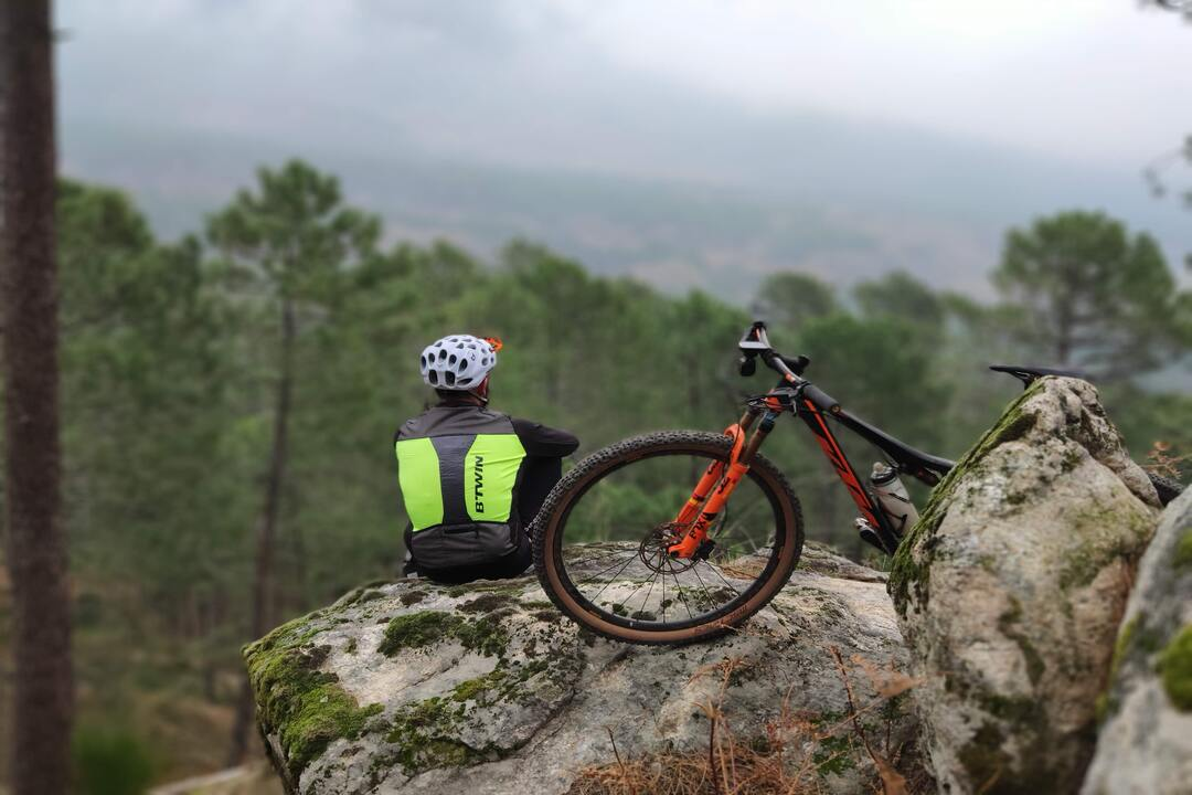 Esportes na montanha: homem sentando em pedra ao lado de bicicleta