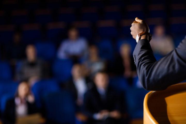 Educação de qualidade no Interior de SP: imagem fechada em braço de homem usando terno de frente para plateia desfocada