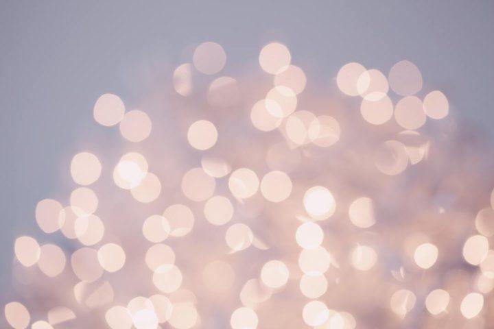 Imagem ilustrativa mostra luzes refletidas em fundo neutro, representando as festas em Angra dos Reis