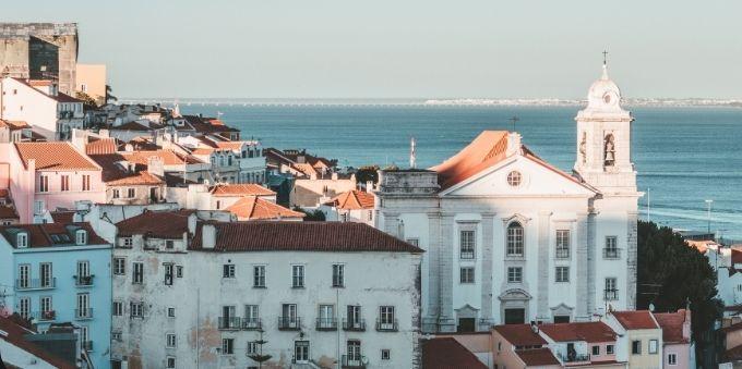 Imagem mostra prédios e igreja tradicionais no bairro Alfama, na pequena Lisboa