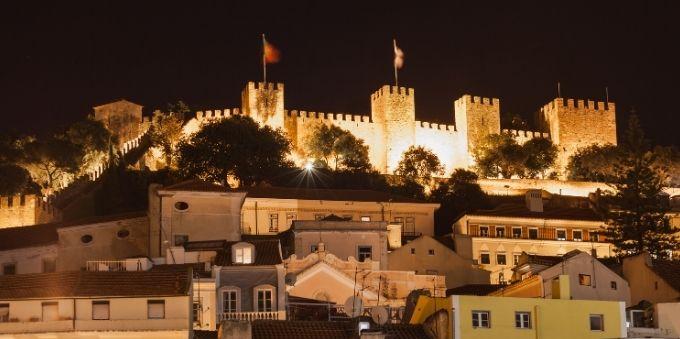 Imagem noturna do Castelo de São Jorge iluminado por luzes