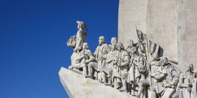 Imagem a ceú aberto de monumento de pedra mostrando desbravadores, como forma de homenagem, em Lisboa