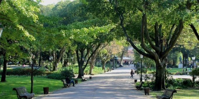 Imagem mostra parque, com caminha de pedras no meio, bancos e árvores ao redor, em Lisboa