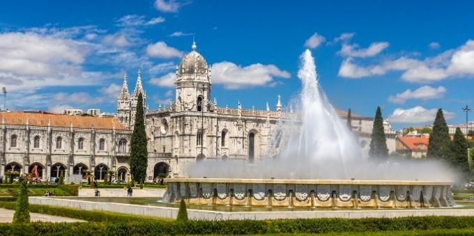 Imagem aberta mostra fachada do mosteiro Jerónimos, em Lisboa, com fonte de água na frente