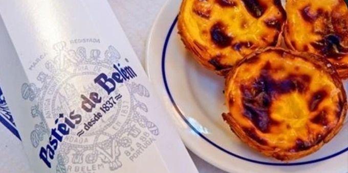 Imagem fechada mostra prato com pastéis de Belém ao lado de guardanapo, em Lisboa