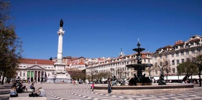 Imagem mostra praça ao céu aberto, com monumento e fonte de água, em Lisboa
