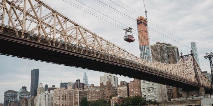 Nova York: imagem aberta de bondinho atravessando cidade ao lado de ponte
