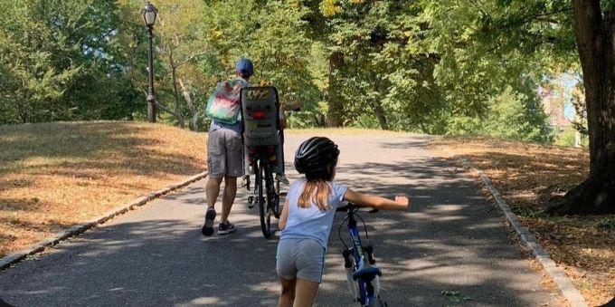 Nova York: imagem mostra homem e menina criança carregando bicicletas pelo parque
