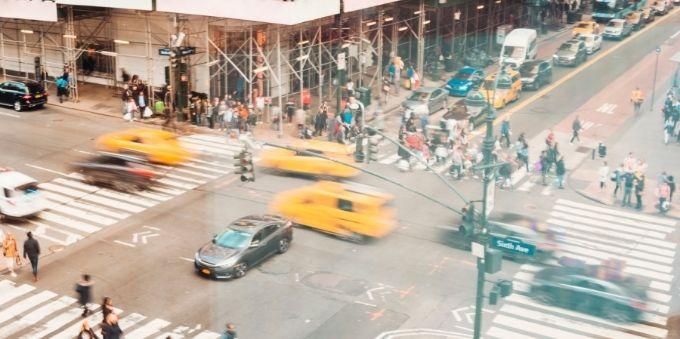 Nova York: imagem desfocada mostra cruzamento, com carros passando rápido e muitas pessoas na rua
