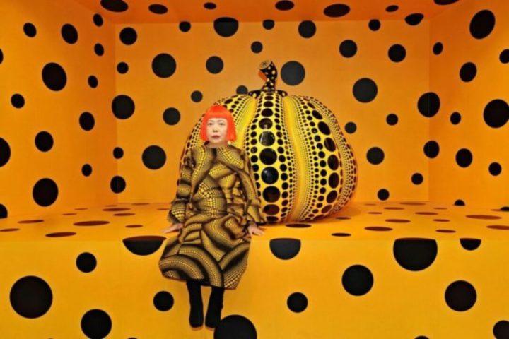imagem da artista Yayoi Kusama em frente a sua obra, em uma exposição em Nova York