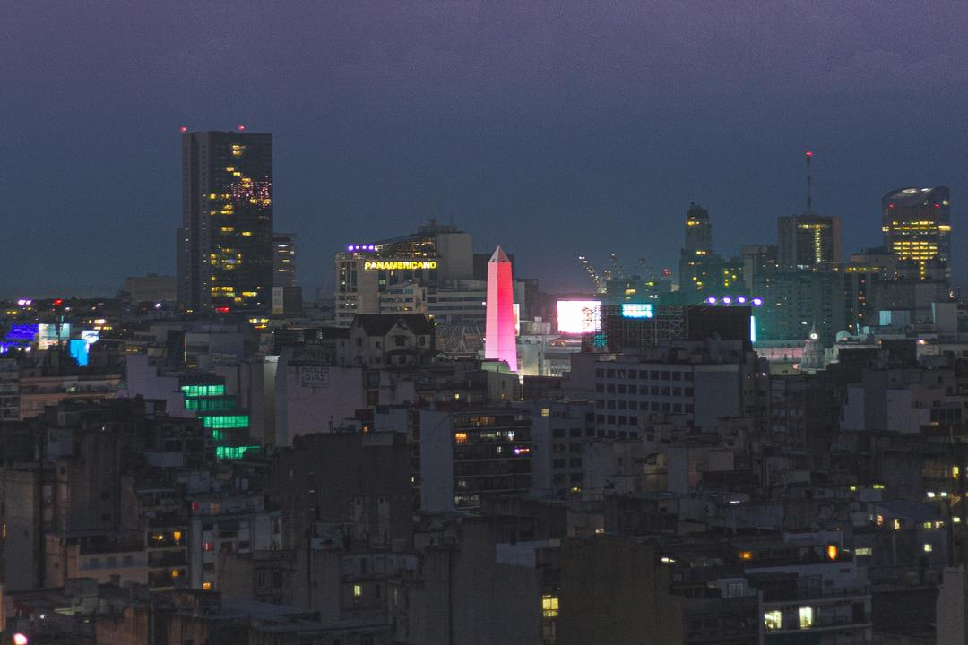 Imagem nortuna, aberta, mostra prédios iluminados na noite em Buenos Aires