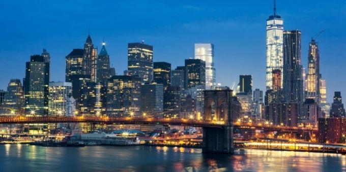 Imagem dos prédios de Nova York iluminados pelas luzes das janelas ao anoitecer