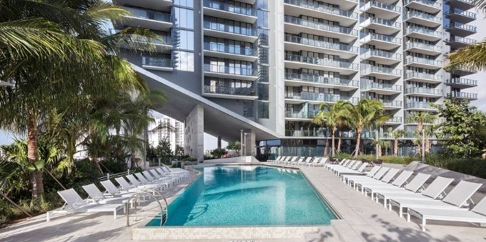 Imagem de área da piscina, com cadeiras para tomar sol ao redor, em hotel em Miami