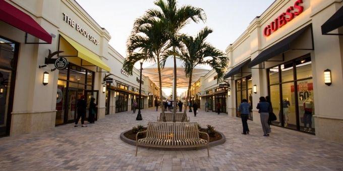 Miami: imagem a ceú aberto mostra pequeno centro comercial, sem muita circulação de pessoas, com árvore no meio