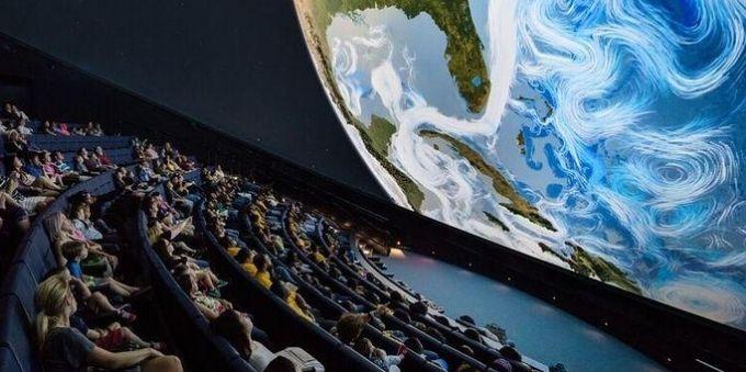 Imagem mostra pessoas sentadas, em sala parecida com a de cinema, e universo sendo projetado em planetário, em Miami.