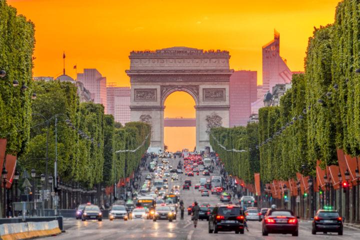 Imagem mostra via movimentada de carros, ao entardecer, com arco no fundo, em Paris