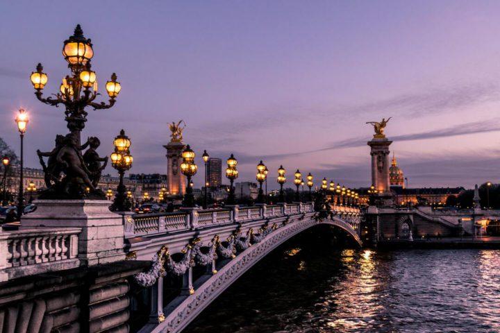 Imagem de ponte iluminada no anoitecer de Paris