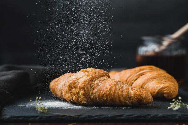 Onde comer em Paris: imagem artística mostra pão em foco e farinha no ar, caindo sobre o pão