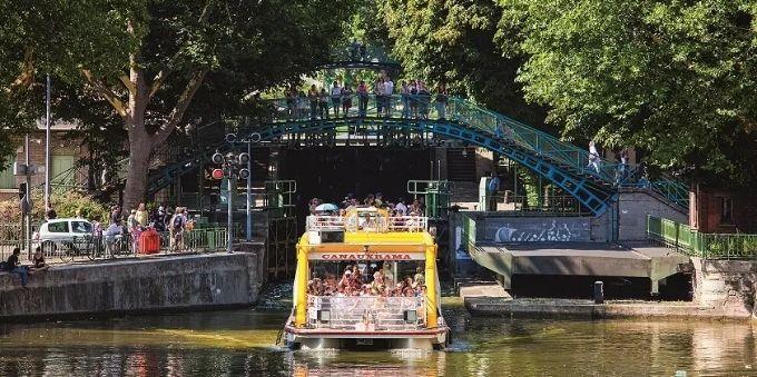Imagem de pessoas passeando dentro de barco no Canal St. Martin em Paris
