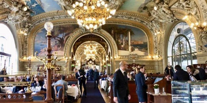 Imagem interna de restaurante chique em Paris mostra pessoas frequentando o local