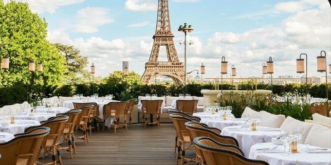 Imagem de mesas de restaurantes em área externa, com a Torre Eiffel ao fundo, em Paris