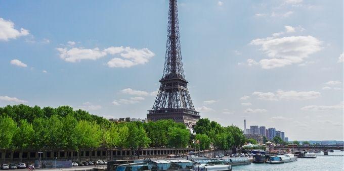 Paris: imagem de Torre Eiffel ao fundo e rio passando na frente, com barcos estacionados