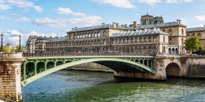 Imagem diurna mostra ponte sobre rio em Paris